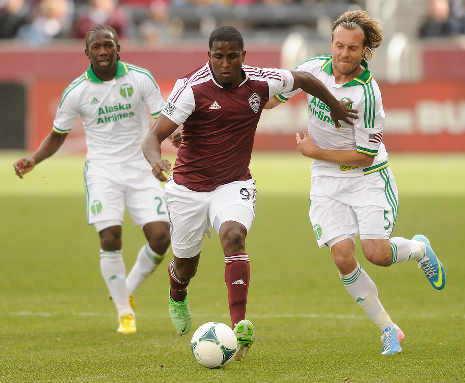 . Edson Buddle (9) of the Colorado Rapids fended off Michael Harrington (5) of the Portland Timbers in the first half. The Colorado Rapids hosted the Portland Timbers Saturday, March 30, 2013 at Dick\'s Sporting Goods Park in Commerce City.  Photo By Karl Gehring/The Denver Post)