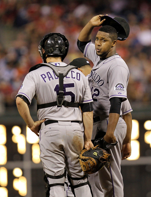 . Colorado Rockies pitcher Juan Nicasio stands next to catcher Jordan Pacheco as he begins to leave the mound after being relieved in the eighth inning of a baseball game against the Philadelphia Phillies, Wednesday, Aug. 21, 2013, in Philadelphia. The Phillies defeated the Rockies 4-3. (AP Photo/Laurence Kesterson)