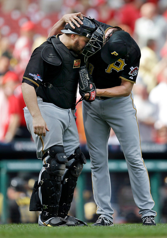 . Pittsburgh Pirates relief pitcher Jason Grilli, right, and catcher Russell Martin, left, celebrate after beating the St. Louis Cardinals 7-1 in Game 2 of baseball\'s National League division series on Friday, Oct. 4, 2013, in St. Louis. The best-of-five games series is tied 1-1. (AP Photo/Jeff Roberson)