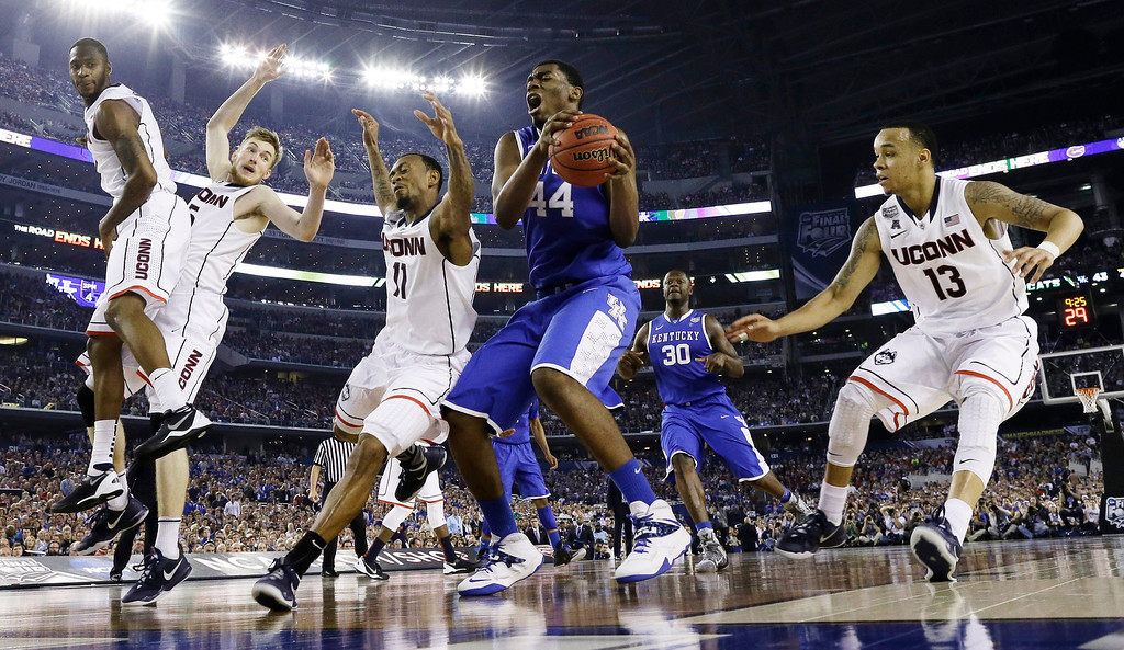 . Kentucky center Dakari Johnson (44) grabs the ball between defenders Connecticut guard Ryan Boatright (11) and guard Shabazz Napier (13) during the second half of the NCAA Final Four tournament college basketball championship game Monday, April 7, 2014, in Arlington, Texas. (AP Photo/David J. Phillip)