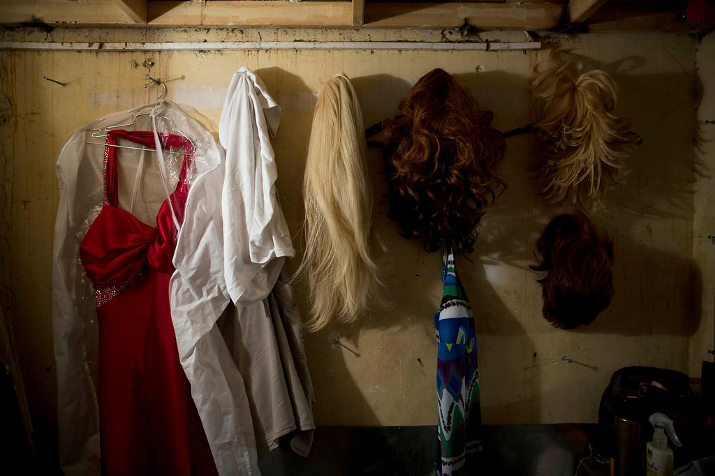 . Israeli Orthodox Jew Shahar Hadar\'s wigs and dress hang in a dressing room just before his drag queen show at a gay club in Jerusalem on on Monday, July 29, 2013. Hadar, a telemarketer by day, has taken the gay Orthodox struggle from the synagogue to the stage, beginning to perform as one of Israel\'s few religious drag queens. His drag persona is that of a rebbetzin, a female rabbinic advisor, a wholesome guise that stands out among the sarcastic and raunchy cast of characters on Israel\'s drag queen circuit. (AP Photo/Oded Balilty)