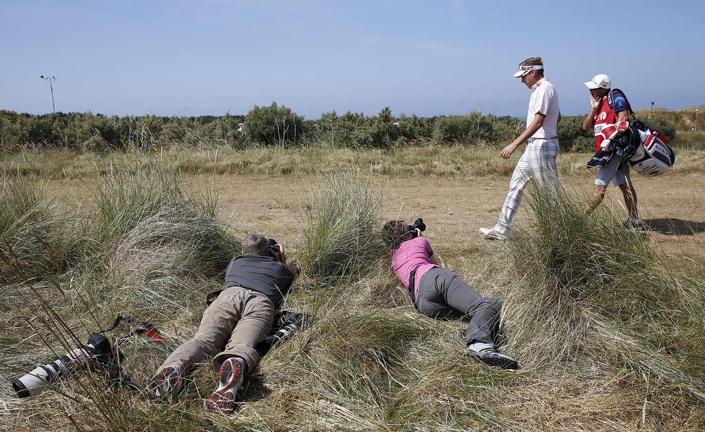 . Photographers take pictures of England\'s Ian Poulter as he walks across a fairway during the third round of the 2013 British Open Golf Championship at Muirfield golf course at Gullane in Scotland on July 20, 2013.  ADRIAN DENNIS/AFP/Getty Images