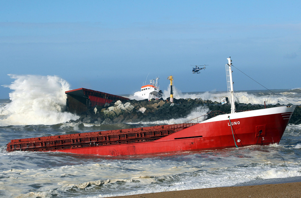 . A helicopter flies over a Spanish cargo ship that slammed into a jetty in choppy Atlantic Ocean waters and broke in two, off Anglet, southwestern France, Wednesday, Feb. 5, 2014.  (AP Photo/Bob Edme)