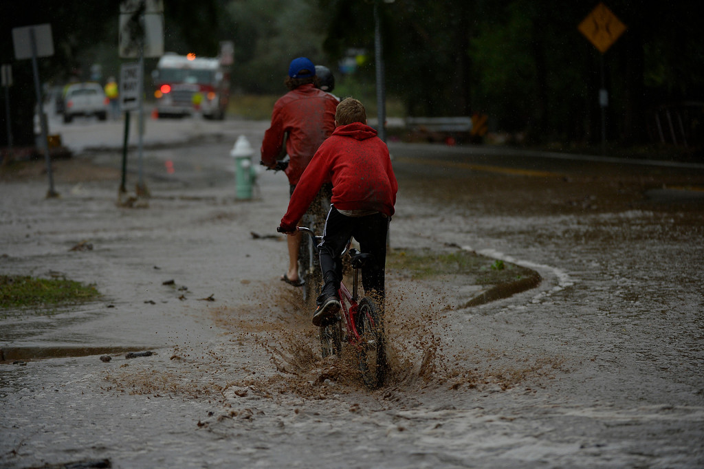 . BOULDER, CO. - September 12: Kids riding through the flood waters along 19th Street after heavy rains caused flash flooding and damage in Boulder September 12, 2013 Boulder, Colorado. (Photo By Joe Amon/The Denver Post)