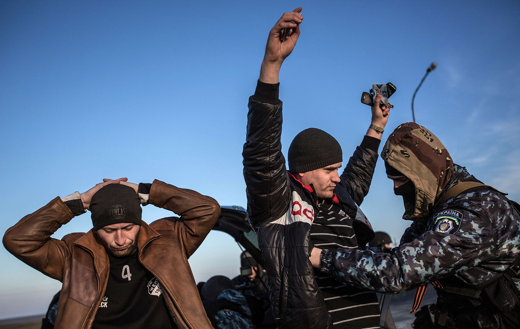 . A man holds his hands up as he is searched by a pro-Russian serviceman at Chongar checkpoint blocking the entrance to Crimea on March 10, 2014. Russia vowed on March 10 to unveil its own solution to the Ukrainian crisis that would run counter to US efforts and would appear to leave room for Crimea to switch over to Kremlin rule. The unexpected announcement came as Ukraine\'s new pro-European leaders raced to rally Western support in the face of the seizure by Kremlin-backed forces of the strategic Black Sea peninsula and plans to hold a Sunday referendum on switching Crimea\'s allegiance from Kiev to Moscow. ALISA BOROVIKOVA/AFP/Getty Images