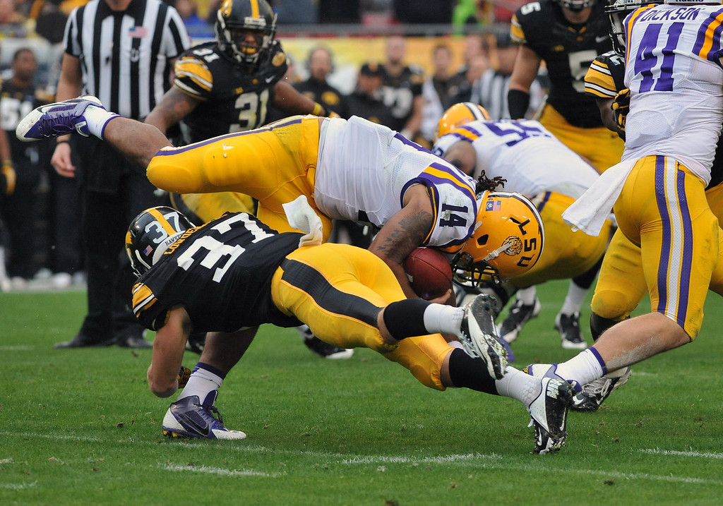 . Running back Terrence Magee #14 of the LSU Tigers rushes upfield in the first half against John Lowdermilk #37 of the Iowa Hawkeyes January 1, 2014  in the Outback Bowl at Raymond James Stadium in Tampa, Florida.  (Photo by Al Messerschmidt/Getty Images)