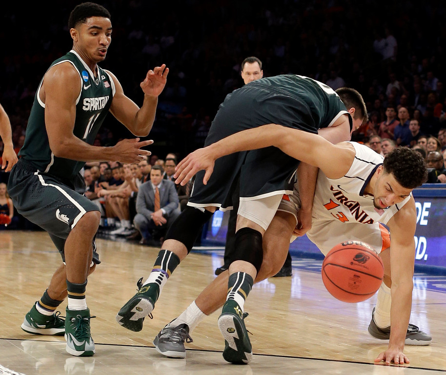 . Virginia forward Anthony Gill, right, gets wrapped up with Michigan State forward Kenny Kaminski while competing for a loose ball during the first half in a regional semifinal at the NCAA men\'s college basketball tournament, Friday, March 28, 2014, in New York. Michigan State guard Gary Harris watches. (AP Photo/Frank Franklin II)