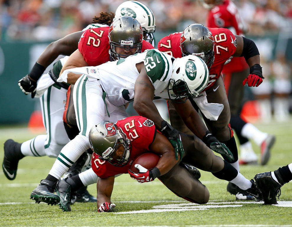 . EAST RUTHERFORD, NJ - SEPTEMBER 8:   David Harris #52 of the New York Jets takes down Doug Martin #22 of the Tampa Bay Buccaneers during their game at MetLife Stadium on September 8, 2013 in East Rutherford, New Jersey.  (Photo by Jeff Zelevansky/Getty Images)