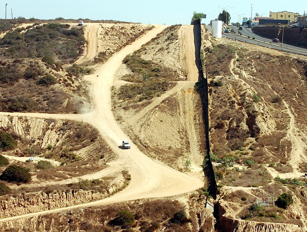 . A U.S. Border Patrol vehicle goes down a steep road along the the U.S./Mexico border above Smuggler\'s Gulch in Imperial Beach, Calif., Oct. 14, 2003. The federal government and a powerful local Republican congressman have been pushing for years to fortify the 3 1/2-mile stretch of border just north of Tijuana. Their plan is opposed by California coastal regulators and environmentalists who say it could harm a fragile Pacific estuary. Now supporters may be getting closer to victory. (AP Photo/Denis Poroy, File)
