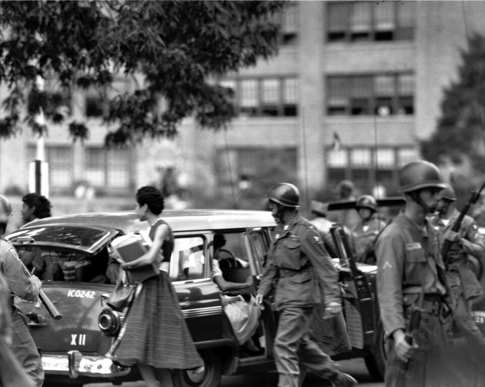 . Federal troops escort black students as they arrive in a U.S. Army station wagon at Central High School in Little Rock, Ark., during the first week of integration in Sept. 1957.  (AP Photo)