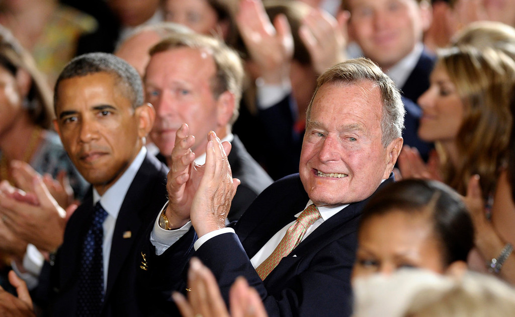 """. Former President George H. W. Bush sitting next to President Barack Obama, left, recognizes a member of the audience after presenting the 5,000th Daily Point of Light Award in the East Room of the White House of the White House in Washington, Monday, July 15, 2013. Obama welcomed Bush to the White House in a salute to public service and to the drive for volunteerism that the 41st president inspired with his \""""thousand points of light\"""" initiative more than two decades ago.  (AP Photo/Susan Walsh)"""