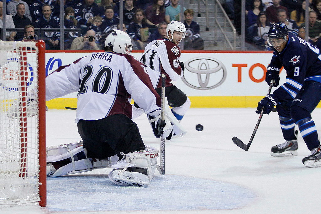 . Winnipeg Jets\' Evander Kane (9) scores on Colorado Avalanche goaltender Reto Berra (20) as Andre Benoit (61) watches during the second period of an NHL hockey game Wednesday, March 19, 2014, in Winnipeg, Manitoba. (AP Photo/The Canadian Press, John Woods)