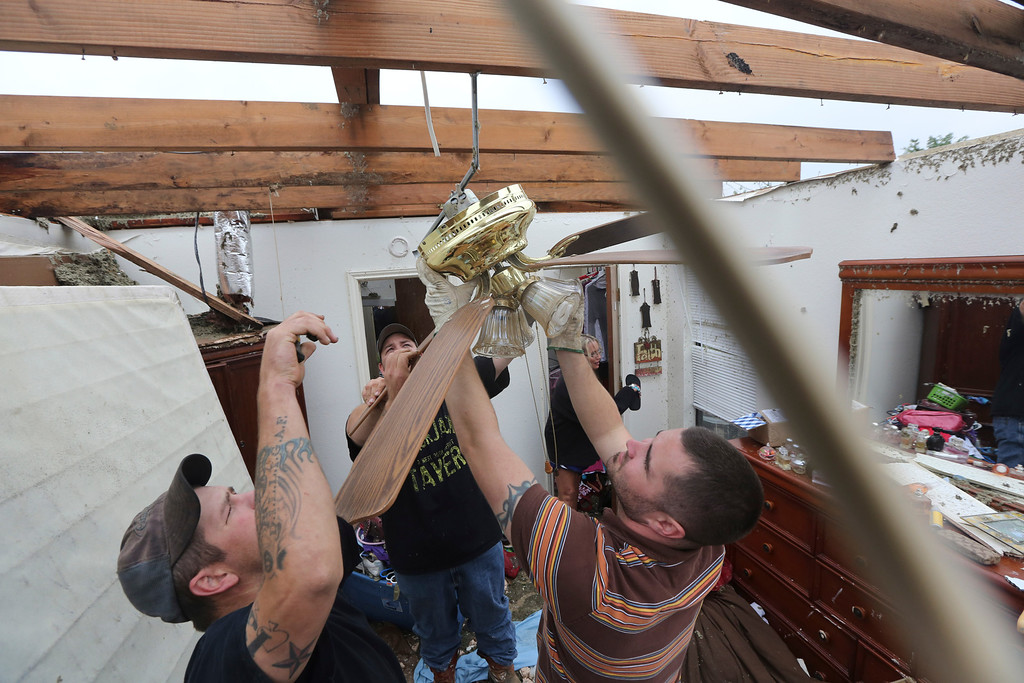 . Derrek Girsham, right, Jeremy Hulce, left, and Dustin Seay cut down a fan as they start cleaning up a home that was destroyed by a tornado in Cleburne, Texas, Thursday, May 16, 2013. (AP Photo/LM Otero)