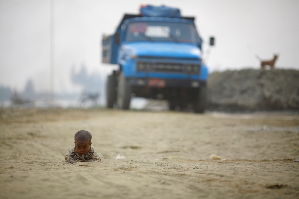 . A child plays on the road near the bank of Yangon River March 18, 2012. REUTERS/Staff