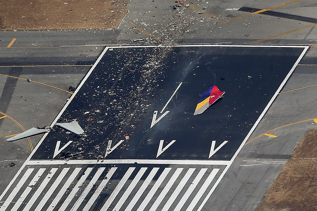 . Debris from an Asiana Airlines Boeing 777 plane is seen on a runway after it crashed while landing at San Francisco International Airport in California on July 6, 2013. Two people were killed and 130 were hospitalized after the plane crash-landed at San Francisco International Airport on Saturday morning, San Francisco Fire Department Chief Joanna Hayes-White said. The figures cited by Hayes-White leave 69 people still unaccounted for in the accident. The Boeing 777, which had flown from Seoul, South Korea, was carrying 307 people.  REUTERS/Jed Jacobsohn