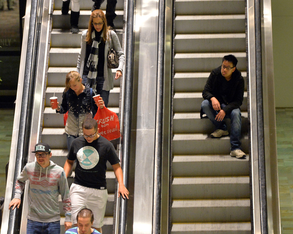 . A shopper rests while going up an escalator at FlatIron Crossing mall on Thanksgiving Day. For more photos and video please see dailycamera.com. November 28, 2013. David R. Jennings/Boulder Daily Camera