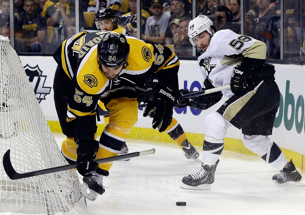. Boston Bruins defenseman Adam McQuaid (54) chases the puck against Pittsburgh Penguins defenseman Kris Letang (58) during the third period in Game 3 of the Eastern Conference finals in the NHL hockey Stanley Cup playoffs, in Boston on Wednesday, June 5, 2013. (AP Photo/Elise Amendola)