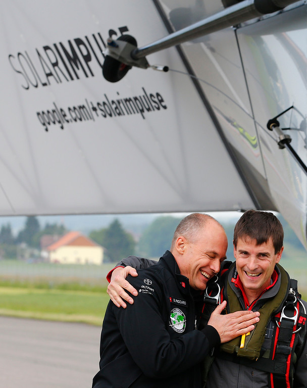 . Solar Impulse co-founder Bertrand Piccard, left, congratulates German test pilot Markus Scherdel, right, after its maiden flight  with the solar-powered Solar Impulse 2 aircraft at its base in Payerne, Switzerland  Monday  June 2, 2014. (AP Photo/Denis Balibouse,Pool)