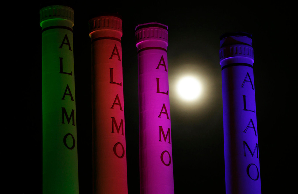 ". A hazy ""super moon\"" is seen behind lighted smoke stacks at the Alamo Quarry Markey, formerly a cement factory, on Saturday, June 22, 2013, in San Antonio. The biggest and brightest full moon of the year graces the sky early Sunday as our celestial neighbor swings closer to Earth than usual. While the moon will appear larger than normal, sky watchers won\'t be able to see the difference with the naked eye.  (AP Photo/Eric Gay)"