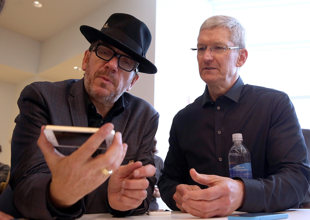. Musician Elvis Costello (L) and Apple CEO Tim Cook look at the new iPhone 5S during an Apple product announcement at the Apple campus on September 10, 2013 in Cupertino, California. T (Photo by Justin Sullivan/Getty Images)