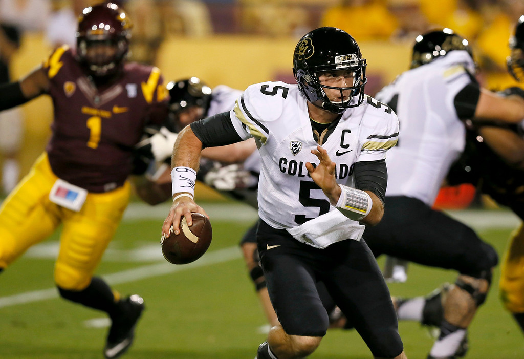 . Colorado\'s Connor Wood (5) is chased out of the pocket by Arizona State\'s Marcus Hardison (1) during the first half of an NCAA college football game on Saturday, Oct. 12, 2013, in Tempe, Ariz. (AP Photo/Ross D. Franklin)