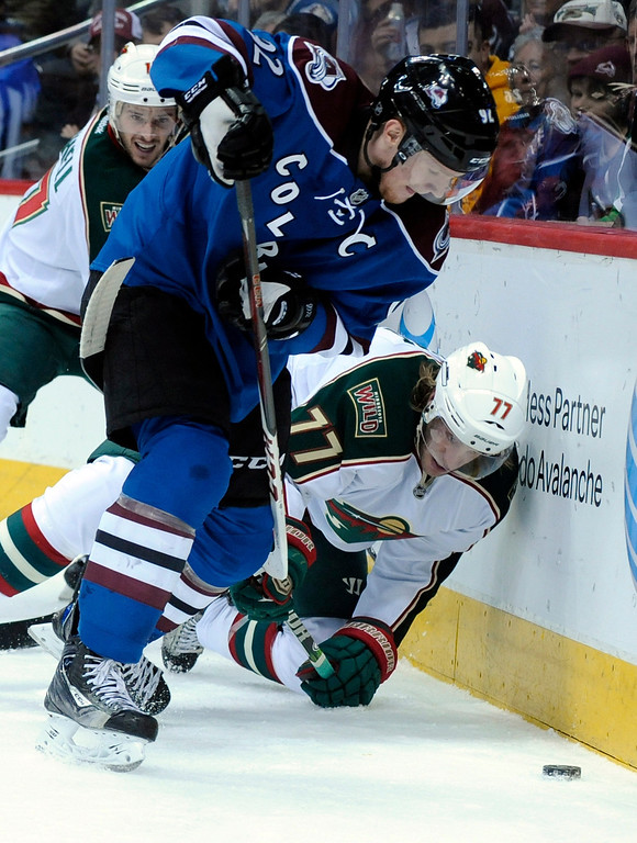 . Colorado Avalanche left wing Gabriel Landeskog (92), from Sweden, fights for the puck with Minnesota Wild defenseman Tom Gilbert (77) during the first period of an NHL hockey game on Saturday, MArch 16, 2013, in Denver. (AP Photo/Jack Dempsey)