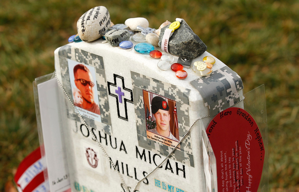 . Photos are seen on the headstone of Joshua Mills in Section 60 at Arlington National Cemetery in Virginia, March 13, 2013. Section 60 contains graves of soldiers from the wars in Iraq and Afghanistan. Picture taken March 13, 2013. REUTERS/Kevin Lamarque