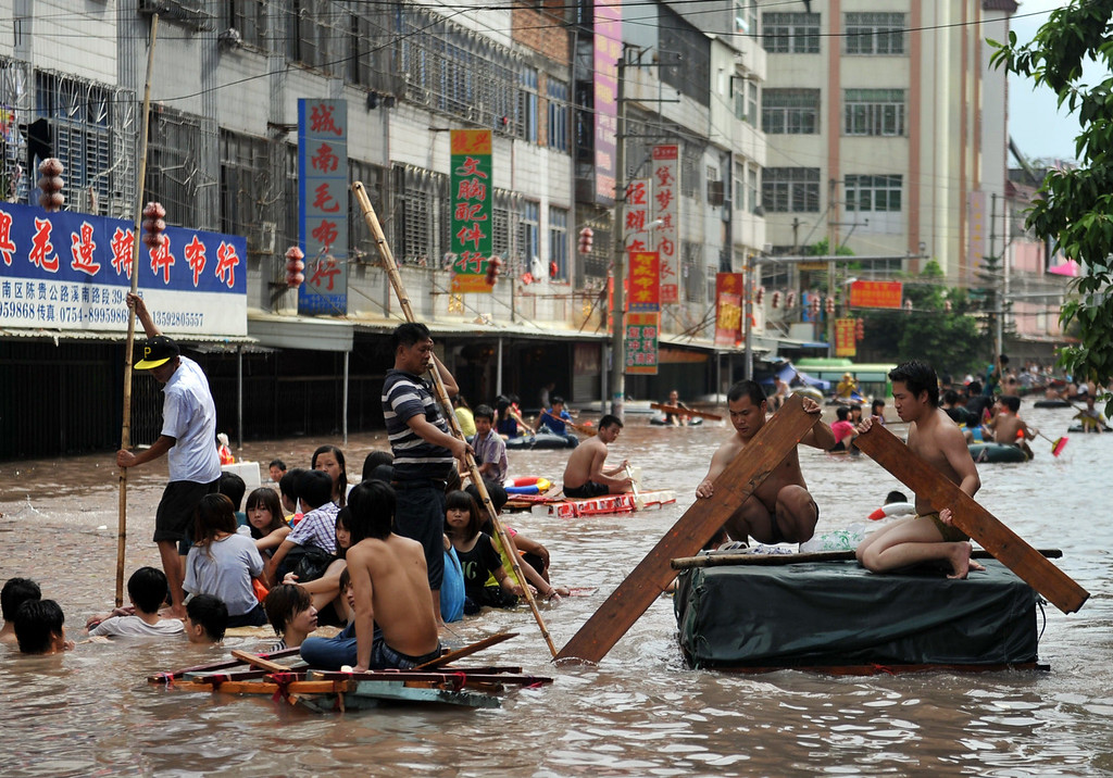 . Residents making their way through flooded streets in the Chaonan district of Shantou, in southern China\'s Guangdong province on August 19, 2013.  Devastating floods at opposite ends of China have left 105 people dead and another 115 missing in recent days, state media said on August 19.   AFP PHOTOSTR/AFP/Getty Images
