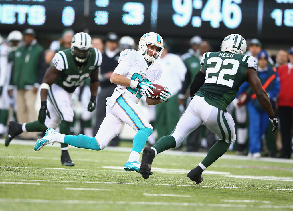 . Brian Hartline #82 of the Miami Dolphins eludes the tackle of  Aaron Berry #22 of the New York Jets and scores a touchdown during their game at MetLife Stadium on December 1, 2013 in East Rutherford, New Jersey.  (Photo by Al Bello/Getty Images)