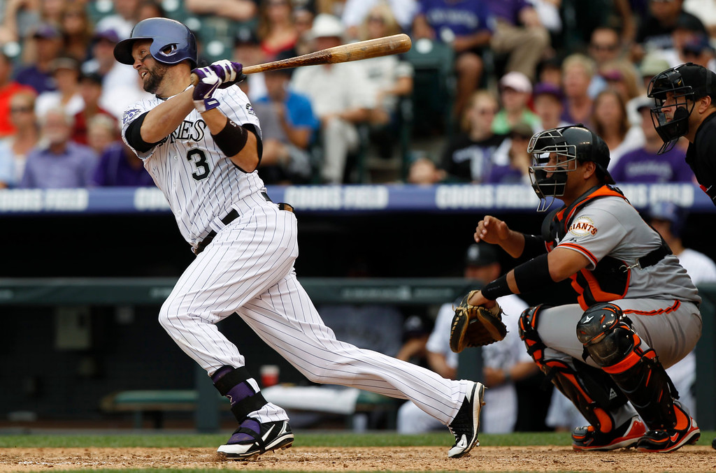 . Colorado Rockies\' Michael Cudyer, left, singles as San Francisco Giants catcher Guillermo Quiroz looks on in the eighth inning of the Giants\' 5-2 victory in a baseball game in Denver on Sunday, June 30, 2013. The single extended Cuddyer\'s hitting streak to 27 games.  (AP Photo/David Zalubowski)