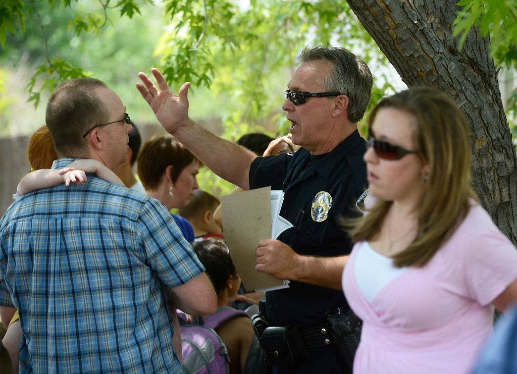 . A Westminster police officer talks with neighbors near the scene of the house house explosion on Ingalls Street in Westminster, Colorado.  (Photo By Andy Cross/The Denver Post)