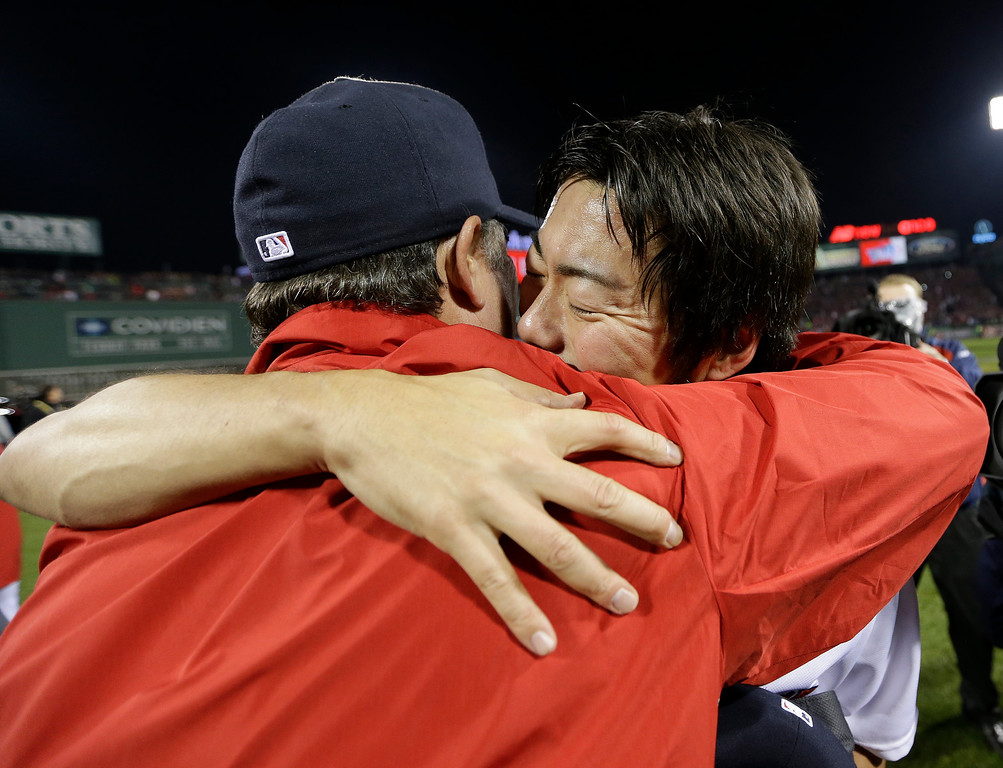 . Boston Red Sox manager John Farrell hugs relief pitcher Koji Uehara after Boston defeated the St. Louis Cardinals in Game 6 of baseball\'s World Series Wednesday, Oct. 30, 2013, in Boston. The Red Sox won 6-1 to win the series. (AP Photo/David J. Phillip)