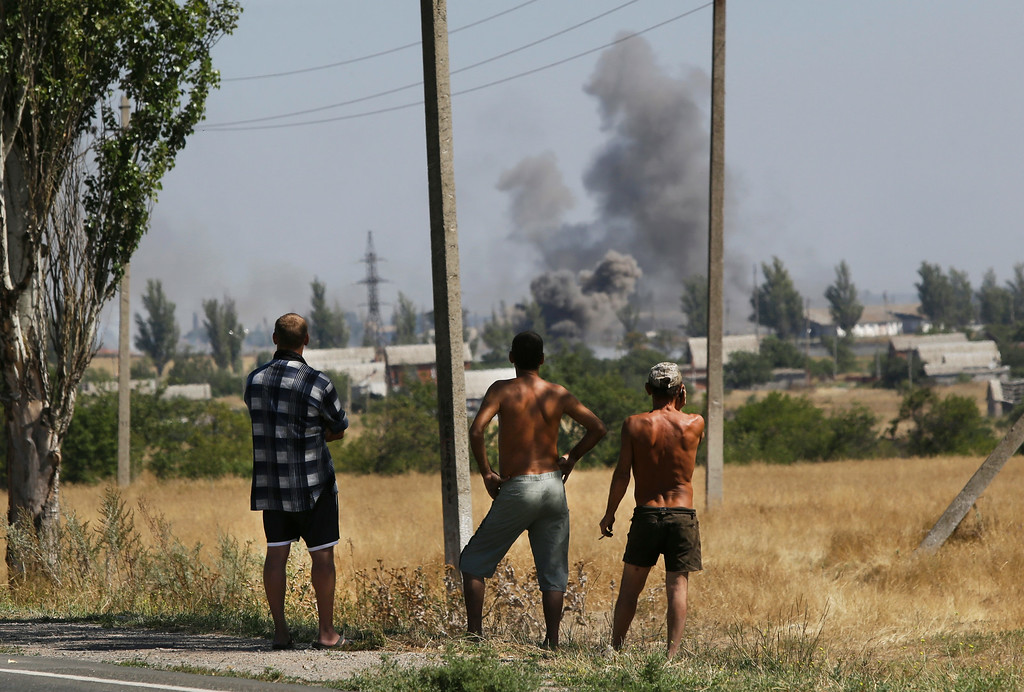 . Local residents watch as smoke rises, during shelling, in the town of Novoazovsk, eastern Ukraine, Wednesday, Aug. 27, 2014. Separatist rebels shelled a town in southeastern Ukraine on Wednesday, raising fears they are launching a counter-offensive on government-held parts of the region, one day after the leaders of Ukraine and Russia met to discuss the escalating crisis. (AP Photo/Sergei Grits)