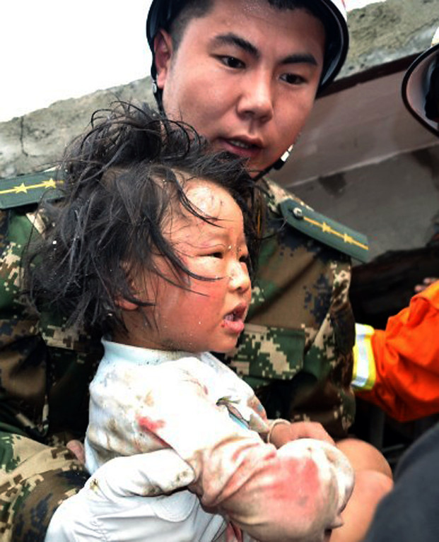 . A rescuer carries a child to safety after she was pulled out of her collapsed home after an earthquake hit Ya\'an City in Lushan county, southwest China\'s Sichuan province on April 20, 2013. More than 100 people were killed and 3,000 injured when a strong earthquake shook southwest China on April 20, wrecking homes and triggering landslides in an area devastated by a major tremor in 2008. AFP PHOTOSTR/AFP/Getty Images