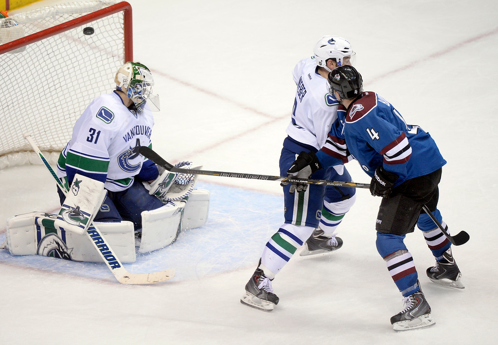 . Tyson Barrie (4) lifted a shot over the shoulder of Vancouver goaltender Eddie Lack (31) for a goal in overtime. The Colorado Avalanche defeated the Vancouver Canucks 3-2 in overtime Thursday night, March 27, 2014 at the Pepsi Center in Denver, Colorado. (Photo by Karl Gehring/The Denver Post)