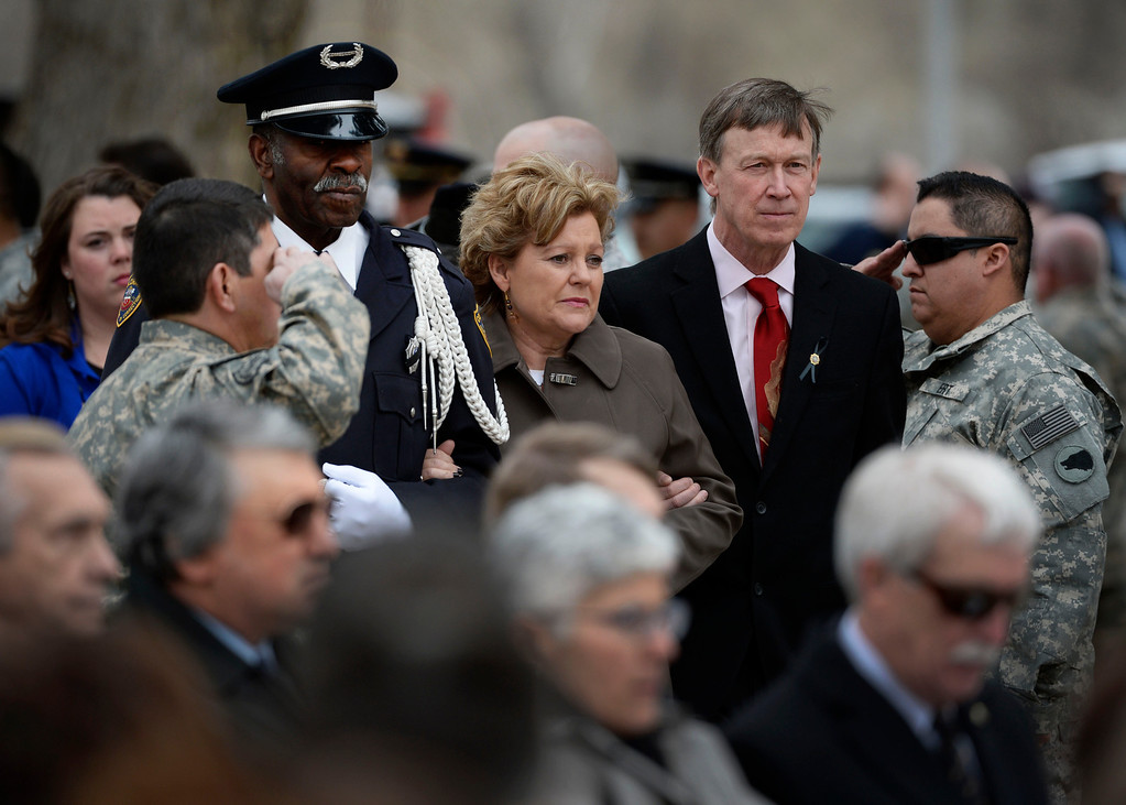 . Colorado Department of Corrections Honor Guard member, Harry Campbell, left, along with Colorado Governor, John Hickenlooper, right, escort Lisa Clements, center, to the Colorado Department of Corrections Fallen Officer Memorial honoring Lisa\'s husband, the head of the DOC, Tom Clements at the Territorial Correctional Facility park Saturday morning, March 15, 2014. Clements was killed March 19, 2013 at his home by Evan Ebel. Clements\' name was added to the memorial and a tree was planted in his name.  (Photo By Andy Cross / The Denver Post)