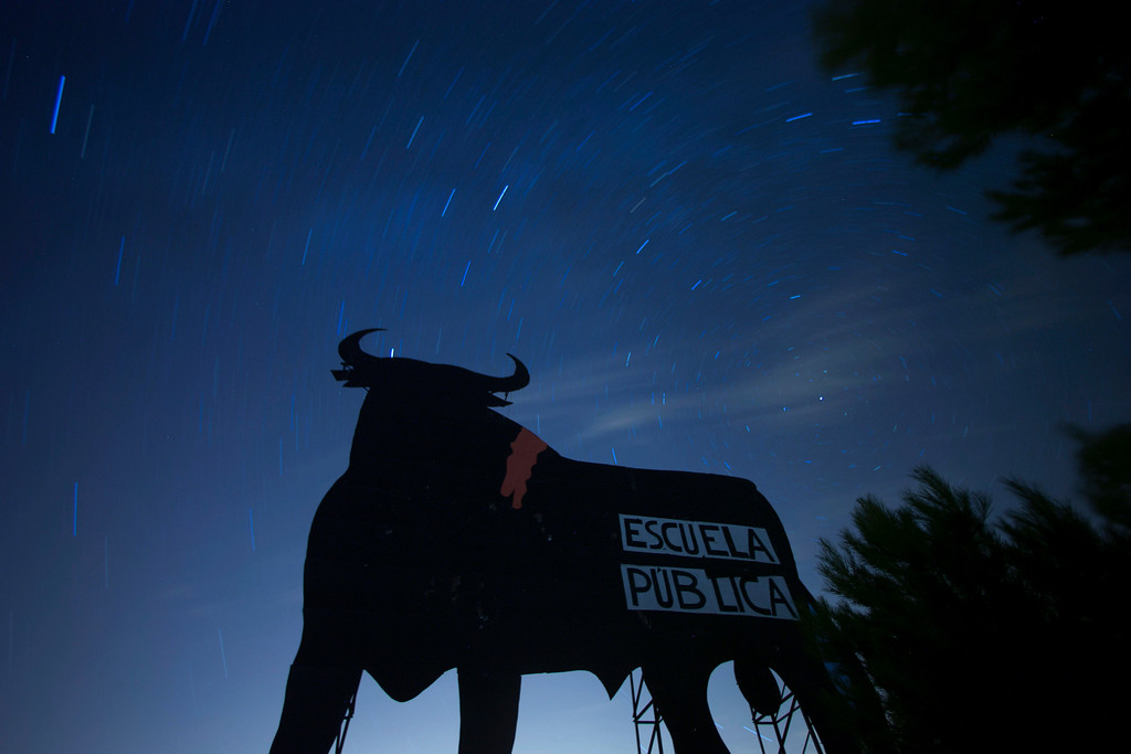 """. Stars seen as streaks from a long camera exposure are seen behind and above a roadside silhouette of a Spanish fighting bull, conceived decades ago as highway billboards, in Villarejo de Salvanes, central Spain,  2013. A sign on the bull, put up by protesters, reads \""""State schools\"""" as a reference for a demand for the state funded schools to continue. (AP Photo/Paul White)"""
