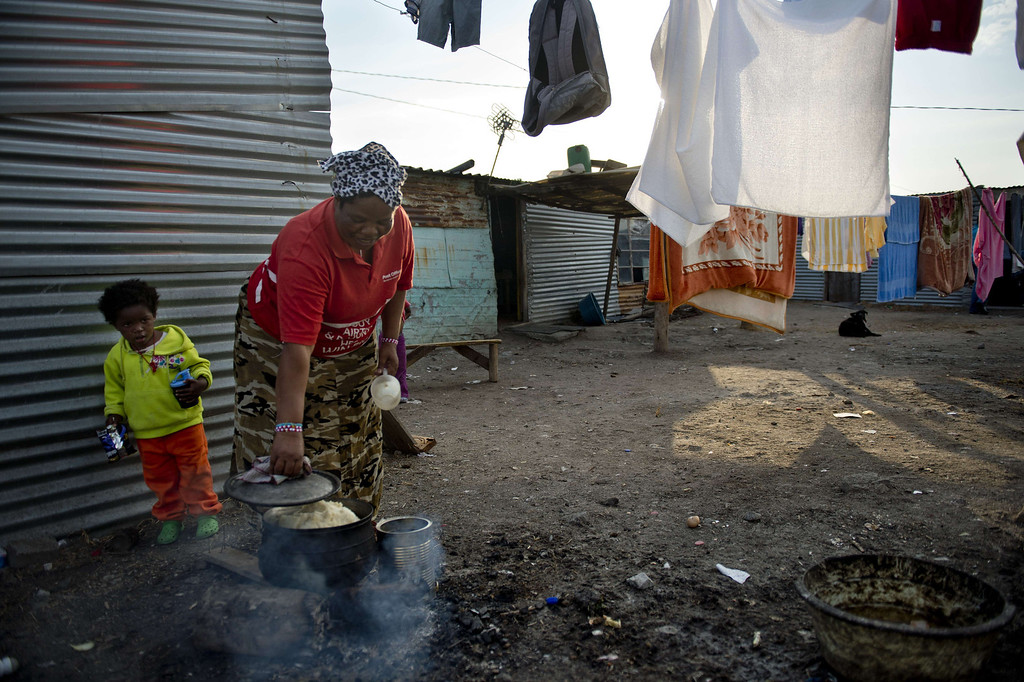 . A woman cooks on July 9, 2013 in the Nkaneng shantytown next to the platinum mine, run by British company Lonmin, in Marikana. On August 16, 2012, police at the Marikana mine open fire on striking workers, killing 34 and injuring 78, during a strike was for better wages and living conditions. Miners still live in dire conditions despite a small wage increase.  ODD ANDERSEN/AFP/Getty Images