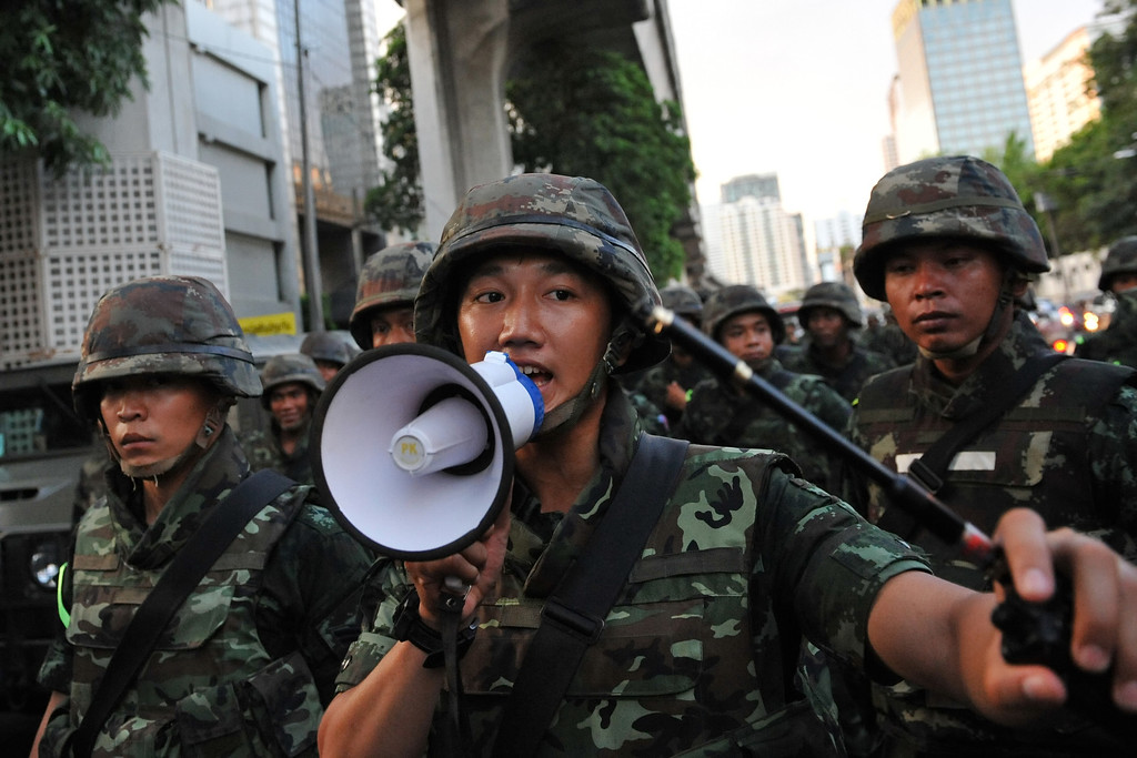 . Thai army soldiers advance towards protesters holding an anti-coup rally on May 23, 2014 in Bangkok, Thailand. Anti-coup protesters rallied in Bangkok\'s shopping district, a day after the military seized control in a bloodless coup. Martial law imposes a 10pm to 5am curfew and public assembly is banned. (Photo by Rufus Cox/Getty Images)