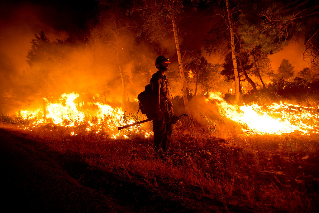 . Idaho City Hotshots firefighter Chance Harrington, from Boise pauses with a drip torch while helping light at back burn near Pine, Idaho while fighting the Elk fire Wednesday Aug. 14, 2013.   (AP Photo/Idaho Statesman, Kyle Green)