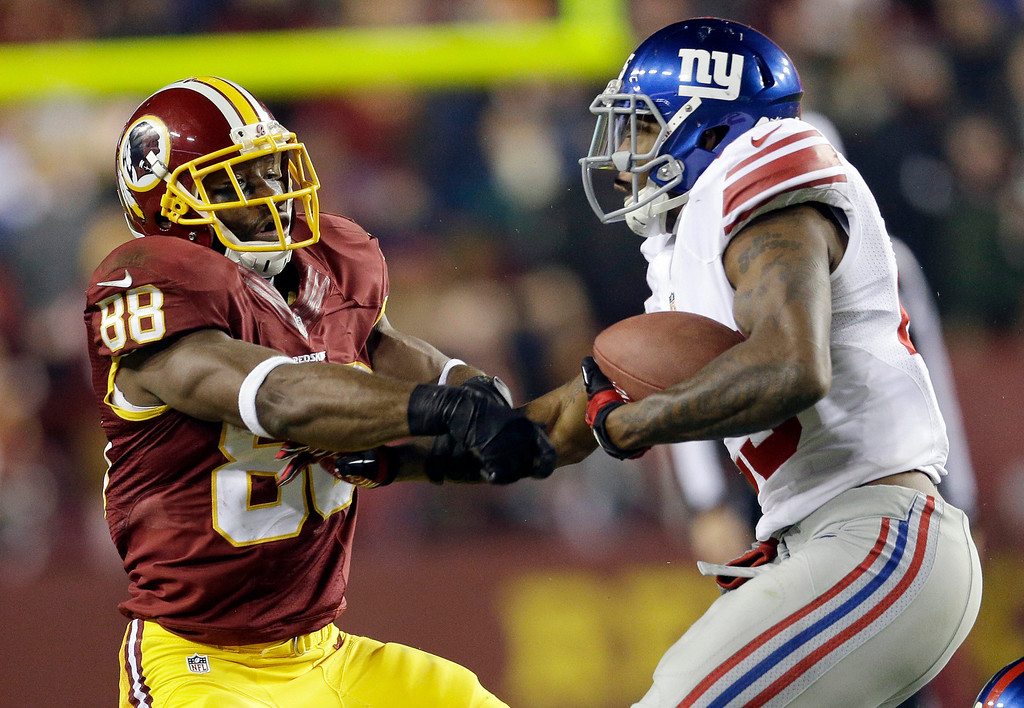 . New York Giants free safety Will Hill, right, takes the football away from Washington Redskins wide receiver Pierre Garcon (88) during the second half of an NFL football game Sunday, Dec. 1, 2013, in Landover, Md. The Giants won 24-17. (AP Photo/Patrick Semansky)