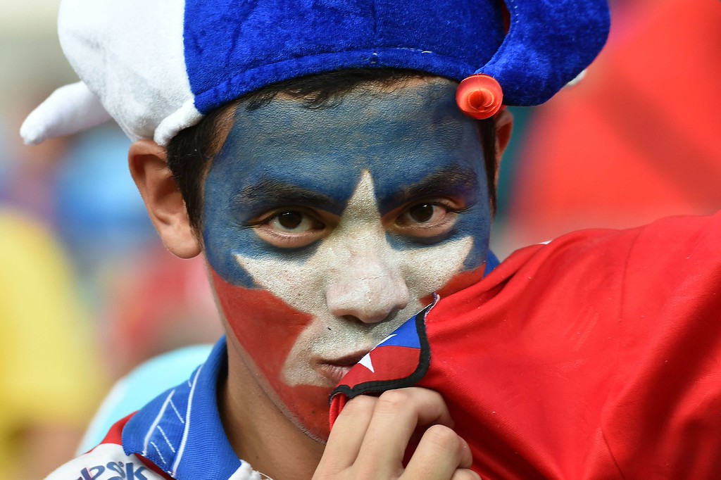 . A Chilean football fan kisses his national flag on his jersey as he waits for the start of the Group B football match between Chile and Australia at the Pantanal Arena in Cuiaba during the 2014 FIFA World Cup on June 13, 2014.  AFP PHOTO / LUIS ACOSTA/AFP/Getty Images