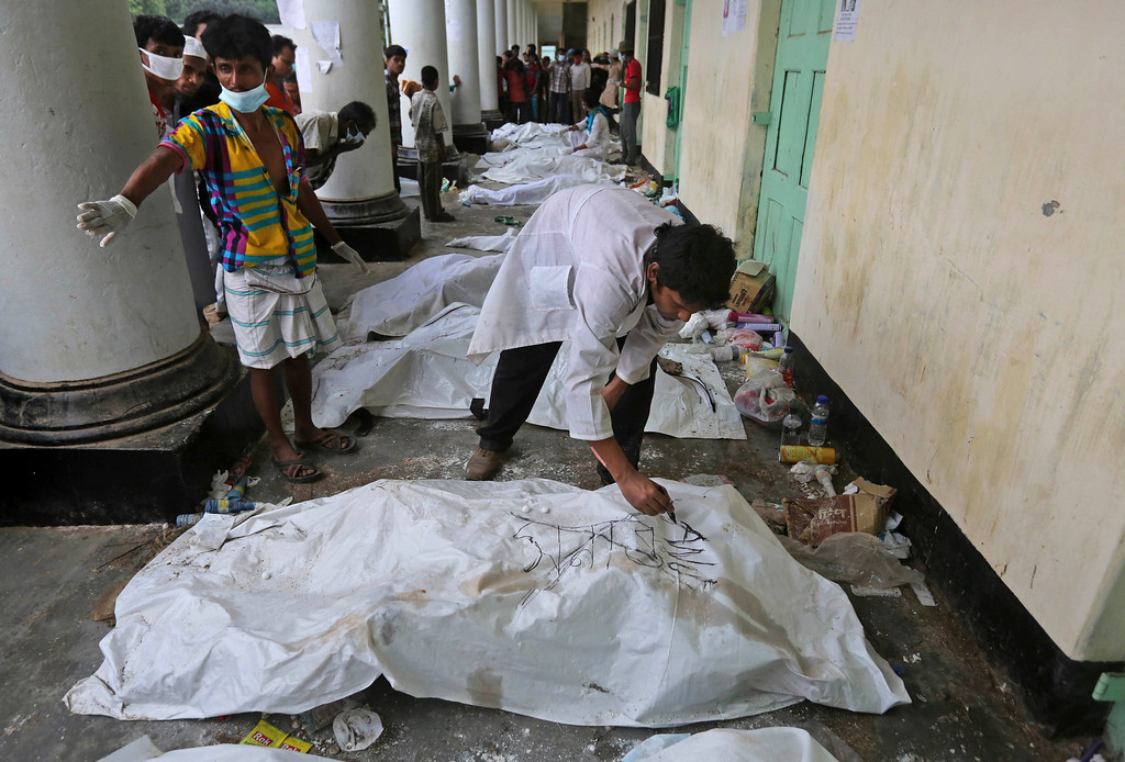 . A Bangladeshi volunteer writes on a body bag  stand over bodies as relatives look for the missing at a makeshift morgue in a schoolyard near a building that collapsed Wednesday in Savar, near Dhaka, Bangladesh, Saturday, April 27, 2013. Police in Bangladesh arrested two owners of a garment factory in a shoddily-constructed building that collapsed this week, killing hundreds of people, as protests spread to a second city Saturday with hundreds of people throwing stones and setting fire to vehicles. (AP Photo/Kevin Frayer)