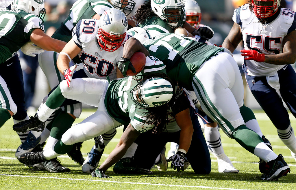 . Rob Ninkovich #50 of the New England Patriots takes down Chris Ivory #33 of the New York Jets during their game at MetLife Stadium on October 20, 2013 in East Rutherford, New Jersey.  (Photo by Jeff Zelevansky/Getty Images)