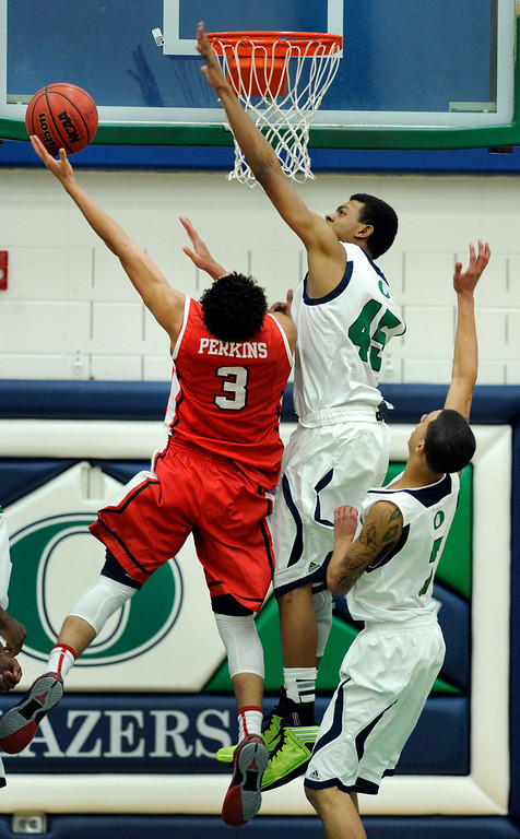 . Blazers center Kingahnah Grant Perry (45)  tried to block a shot from Regis guard Josh Perkins (3) in the second half. The Overland High School boy\'s basketball team defeated Regis Jesuit 80-66 Tuesday night, December 11, 2012.  Karl Gehring/The Denver Post