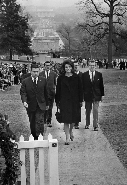 . Jacqueline Kennedy walks to the grave in Arlington National Cemetery on Nov. 28, 1963. Others, from left, are: Pierre Salinger, White House press secretary; Secret Service agent Clinton J. Hill; and presidential aides Jack McNall and Lawrence O\'Brien. Bob Schutz, Associated Press file