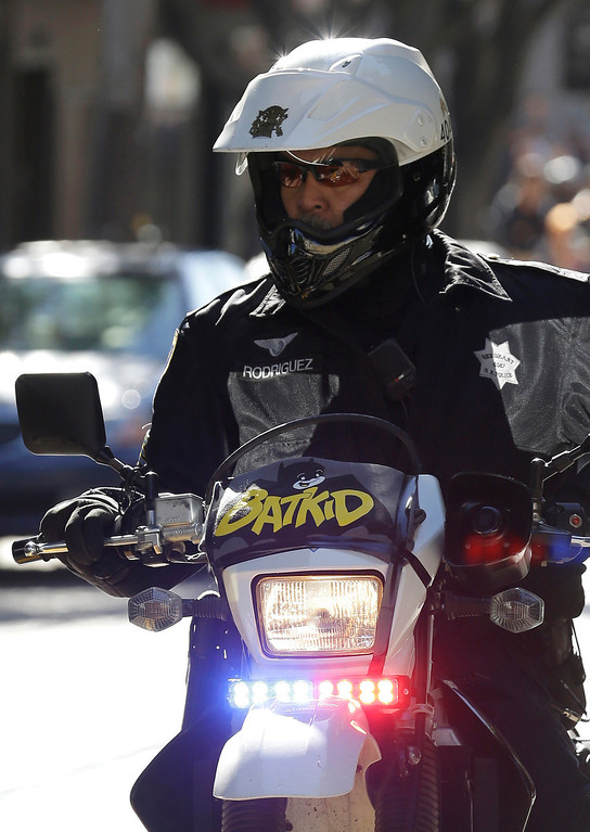 """. A San Francisco Police Officer with a Batkid sign on his bike waits for the arrival of Miles Scott, dressed as Batkid, in San Francisco, Friday, Nov. 15, 2013. San Francisco turned into Gotham City on Friday, as city officials helped fulfill Scott\'s wish to be \""""Batkid.\"""" Scott, a leukemia patient from Tulelake in far Northern California, was called into service on Friday morning by San Francisco Police Chief Greg Suhr to help fight crime, The Greater Bay Area Make-A-Wish Foundation says. (AP Photo/Jeff Chiu)"""