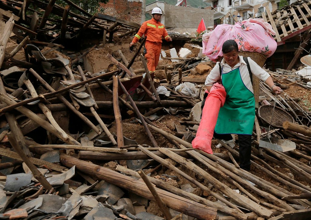 . A villager carries her belongings and walks through the rubbles from destroyed houses following a massive earthquake in the town of Longtoushan in Ludian County in southwest China\'s Yunnan Province Tuesday, Aug. 5, 2014. (AP Photo/Andy Wong)