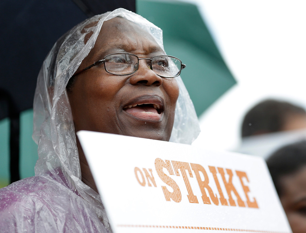 . Ghislaine Bazile chants along with fellow demonstrators demanding higher wages for fast food workers, Thursday, Sept. 4, 2014 in North Miami Beach, Fla. The protests are part of a nationwide day of action targeting the fast food industry. Some 50 activists and workers gathered before dawn outside restaurants in Miami Gardens. Later, more than 100 people convened outside restaurants in North Miami Beach around noon. (AP Photo/Wilfredo Lee)