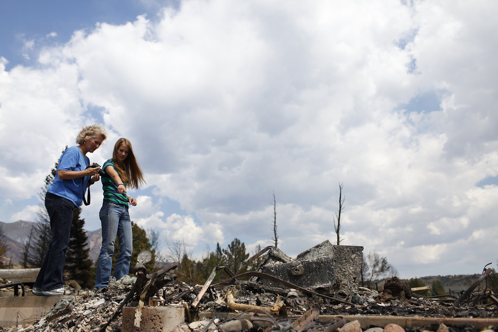 . Carla Albers, left, and her daughter Krista examine the remnants of their home in the Mountain Shadows subdivision on Sunday, July 1, 2012. Their home was one of the more than 350 homes burned in the Waldo Canyon fire. Stephen Mitchell, The Denver Post